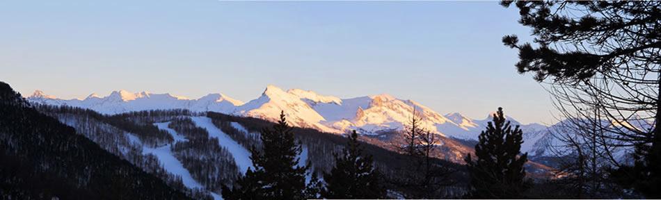 Tramonto sulla montagna coperta di neve una sera d'inverno. Al primo piano le piste di sci di Arvieux.