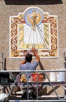 Accroupi, bras levés, l'artiste peignant un cadran solaire à Saint-Véran.